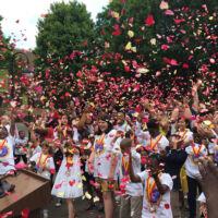 people throwing rose petals in the air