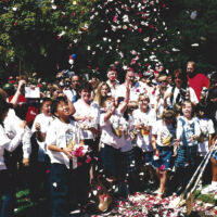 boys and girls in white clothes throwing rose petals in the air