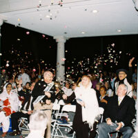 men and women in festive clothes throwing rose petals in the air at nighttime