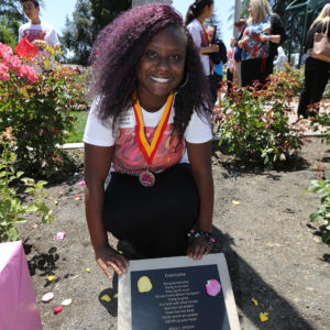 An African-American girls next to a dedication plaque