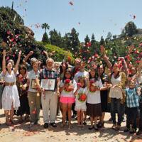men, women and children throwing rose petals in the air