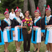 Hmong dancers in national clothes gathered around Silvia holding rose boquet