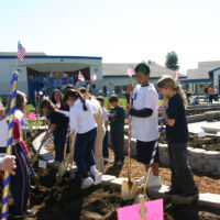 children with shovels are planting roses