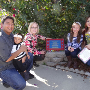 Family gathered around a plaque