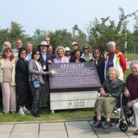 men and women smiling around a garden plaque