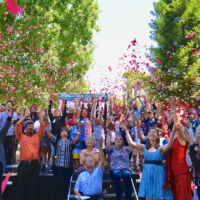 many people tossing rose petals in the air