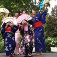 Japanese performers in kimono holding fans and dancing