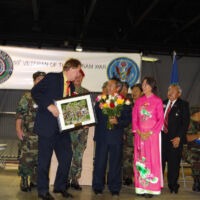 TJ is presenting a plaque to men and women in Chinese national costumes