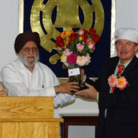 two men in head pieces are holding a vase with roses