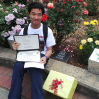 a Chinese student holding certificates of a plaque