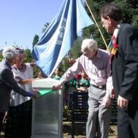 an elderly couple unveiling a plaque