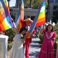 People in festive clothing holding rainbow flags