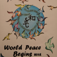 World peace begins with me, many different colored doves flying out of blue cirlce