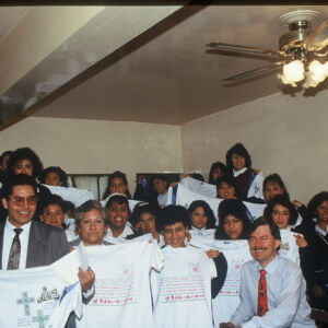 Children and adults wearing white and holding art
