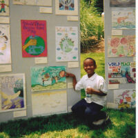 An African- American Boy showing his artwork on an art display