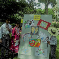 Students in Mexican traditional costumes looking at an art board